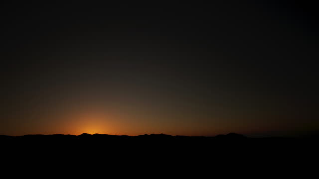 Timelapse sun rises over desert mountains, Dhofar, Oman