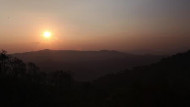 timelapse sun rises over rainforested hills, salu, myanmar - nebbia video stock e b–roll