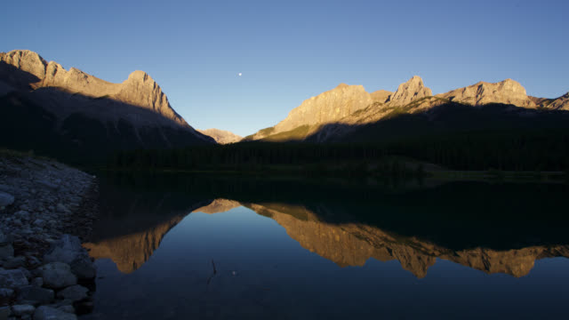 timelapse sun rises over rocky mountains, lake and forest, banff, alberta, canada - canada stock videos & royalty-free footage