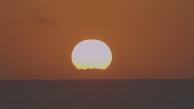 Timelapse WS sun rising through cloud bank above horizon over open sea