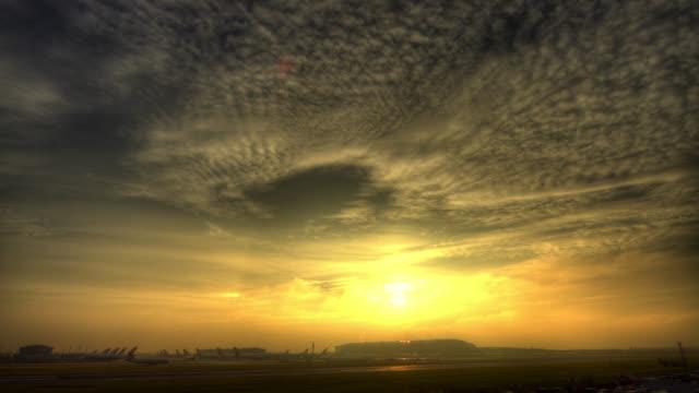 Timelapse sun sets over busy Heathrow airport, London, UK
