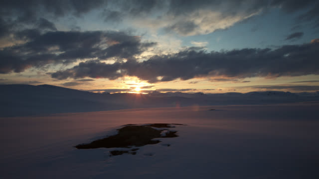 Timelapse sun sets over snowy mountains and tundra, Sweden