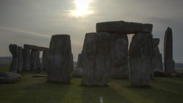 timelapse sun tracks over prehistoric stonehenge monument, wiltshire, uk - stonehenge stock videos and b-roll footage