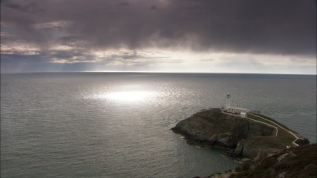 timelapse sunbeams and clouds drift over sea near south stack lighthouse, wales, uk - bedeckter himmel stock-videos und b-roll-filmmaterial