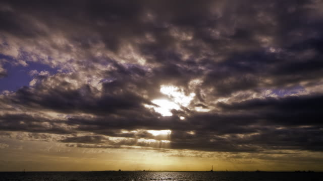 Timelapse sunbeams pass across the water as dusk clouds pass above