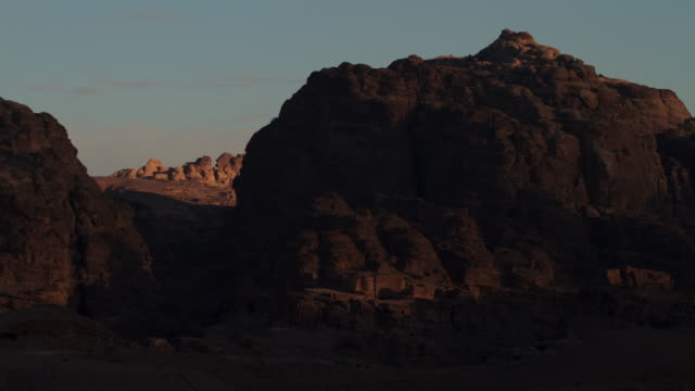 Timelapse sunrise over desert mountains and ruins, Petra, Jordan