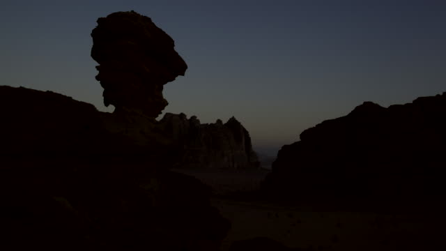 timelapse sunrise over eroded rock stack in desert, wadi rum, jordan - stack rock stock videos and b-roll footage
