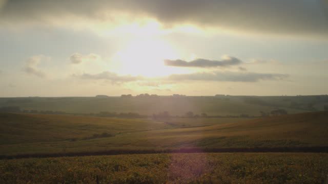 Time-lapse, Sunrise over rural farms, rolling hills and cornfields.