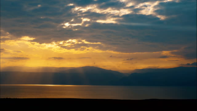 time-lapse/ sunrise over the dead sea, judean desert with jordan mountains in background - dead sea stock videos and b-roll footage