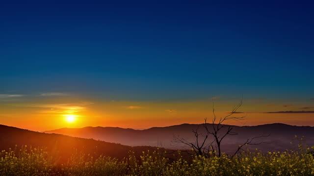 vídeos de stock, filmes e b-roll de timelapse nascer do sol com o movimento de nuvens sobre a montanha - horizonte