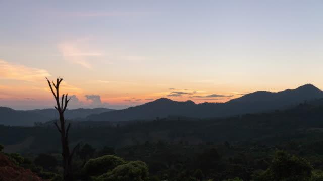 vídeos de stock e filmes b-roll de timelapse sunset behind mountain at phu lanka national park, phayao province, north of thailand. - rasto de estrelas