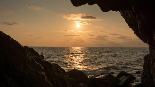timelapse. sunset on the background of stones - cave stock videos & royalty-free footage