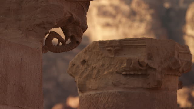 timelapse sunset over ancient pillar with elephant carving, petra, jordan - stein baumaterial stock-videos und b-roll-filmmaterial