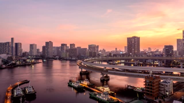 4K timelapse sunset to night view of Tokyo cityscape with many skyscrapers and cruises illuminated over Tokyo bay in Odaiba aera,Tokyo, Japan.