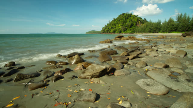 """Timelapse tide goes out on rocky beach, Thailand"""
