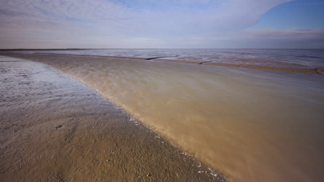 Timelapse tide recedes in channel on mud flats, Norfolk, UK