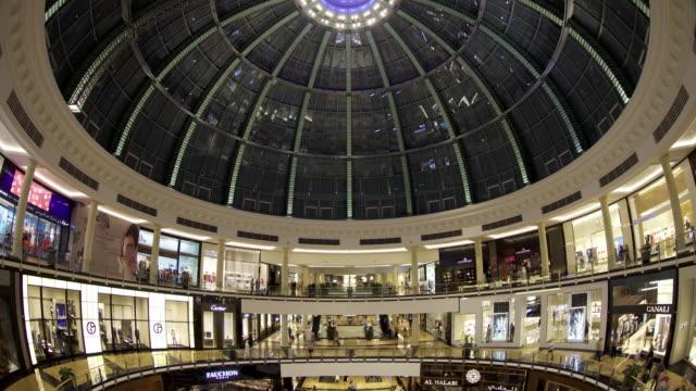 timelapse tilt down over crowds in atrium, mall of the emirates, dubai - einkaufszentrum stock-videos und b-roll-filmmaterial