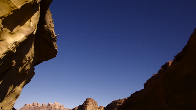 Timelapse tilt over shifting shadows in eroded desert valley, Wadi Rum, Jordan