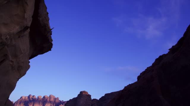 Timelapse tilt over shifting shadows in eroded desert valley, Wadi Rum, Jordan