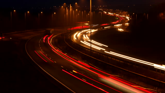 timelapse, tilt up to the lights of road traffic on the busy a14 dual carriageway at night with lightning - tail light stock videos & royalty-free footage