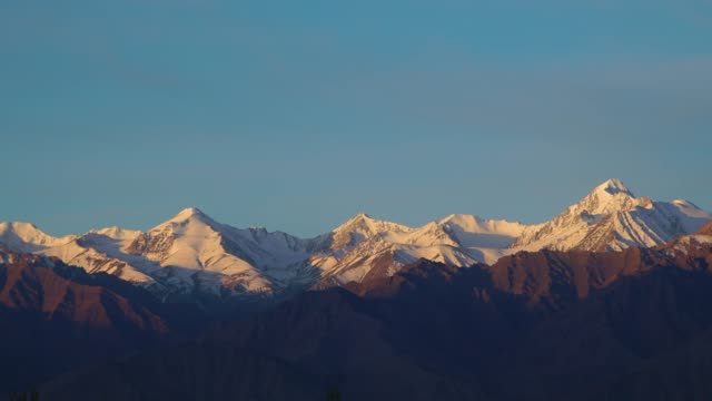 4k ,time-lapse, tilt-down; snow capped mountain at morning in leh, india. - snowing stock videos & royalty-free footage