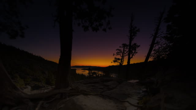 timelapse tilting shot of the sunrise over a emerald bay in nevada with lens flare - nevada stock-videos und b-roll-filmmaterial
