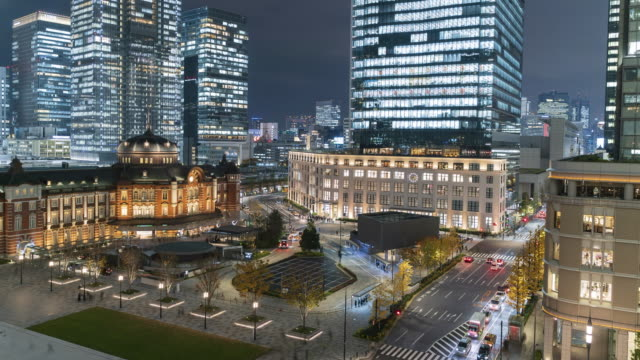 4k time-lapse tokyo station with skyline background and traffic light moving, tokyo, japan. - finanzwirtschaft und industrie stock-videos und b-roll-filmmaterial