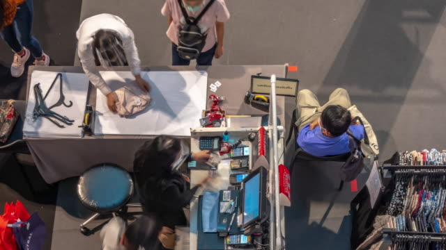 vidéos et rushes de time-lapse vue supérieure de travail de la caisse porter masque et bouclier facial avec le paiement des clients pour leurs achats. - boutique