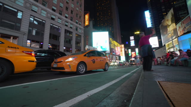 time-lapse: tourists in times square and cars passing by at night in new york, ny - theatre district stock videos & royalty-free footage