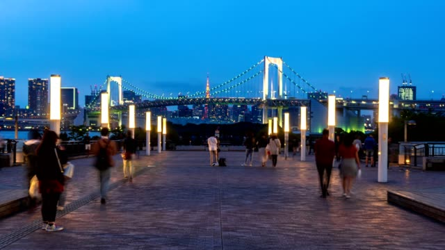 time-lapse: tourists walking and take photo on pedestrain path with rainbow bridge famouse landmark of tokyo, japan - guardare il paesaggio video stock e b–roll