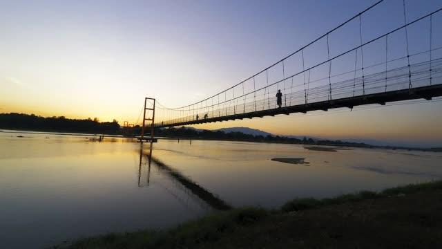 vídeos de stock e filmes b-roll de time-lapse tourists walking on footbridge of suspension bridge to see sunset view on twilight time at tak province thailand - ponte suspensa