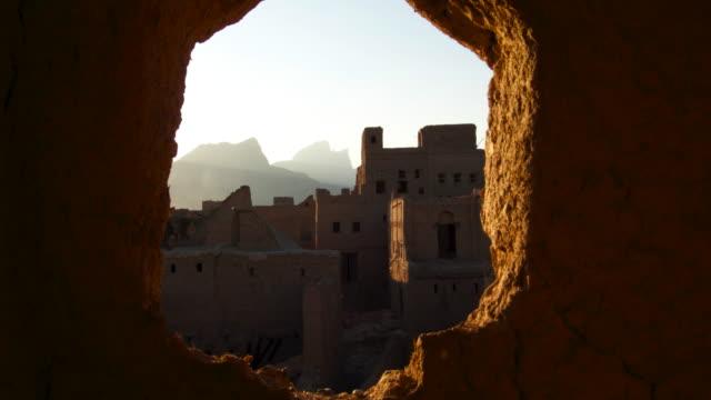 vídeos y material grabado en eventos de stock de timelapse track through hole in wall as sun sets over town, oman - omán