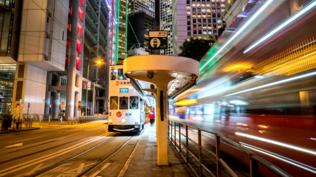4k timelapse - tram station in hong kong central - bus stop stock videos & royalty-free footage