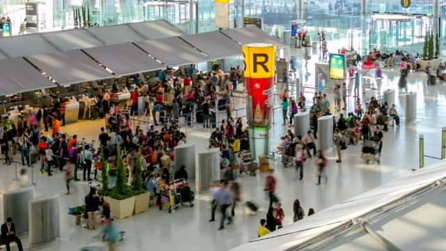 vidéos et rushes de hd time-lapse: foule de voyageurs au comptoir d'enregistrement de l'aéroport - panneau d'entrée