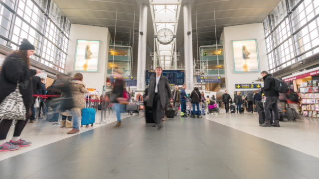 vídeos de stock, filmes e b-roll de multidão de viajante do tempo-lapso no hall de saída do aeroporto copenhague dinamarca - átrio interior de casa