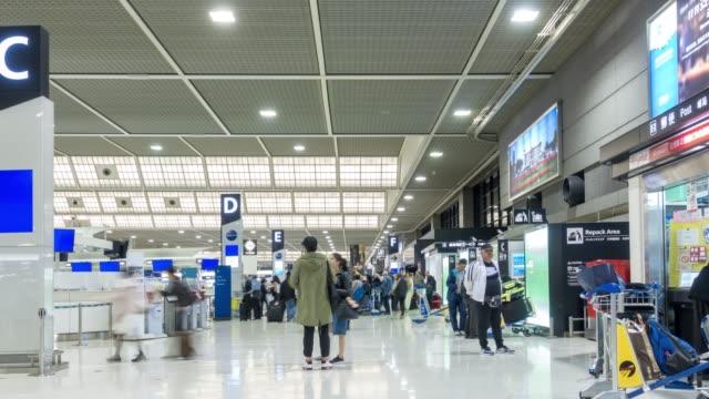 日本の空港出発ターミナル成田でコマ撮り: 旅行者群衆
