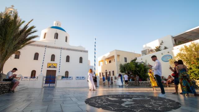 vídeos de stock, filmes e b-roll de time-lapse: multidão do viajante na igreja cristã branca com abóbadas, sinos e por do sol em santorini greece, resolução 4k. - oia santorini