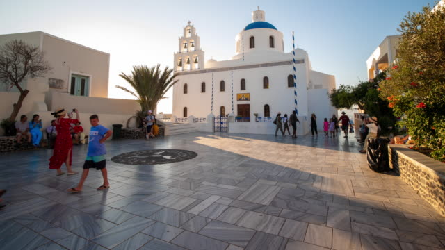 vídeos de stock e filmes b-roll de time-lapse : traveler crowd at white christian church with domes, bells and sunset in santorini greece, 4k resolution. - cubo