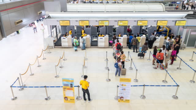 vídeos de stock e filmes b-roll de time-lapse: traveler crowded at airport departure check-in hall - embarcar