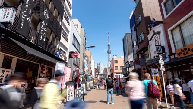 4kタイムラプス:東京・浅草寺周辺の市場に、旅行者の歩行者が押し寄せる。ショットをチルトアップ - スカイツリー点の映像素材/bロール