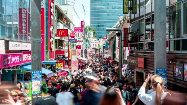 4k タイムラプス:竹下通りに集まる旅行者の歩行者は、東京・原宿駅の有名なファッションショッピングストリートです。 - タイムラプス 点の映像素材/bロール