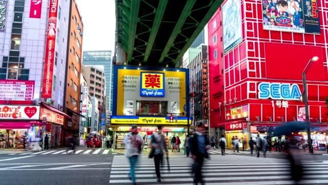 4k time-lapse: traveler pedestrian crowded walking across the crosswalk at akihabara district area, tokyo, japan. tilt down shot - akihabara station stock videos and b-roll footage