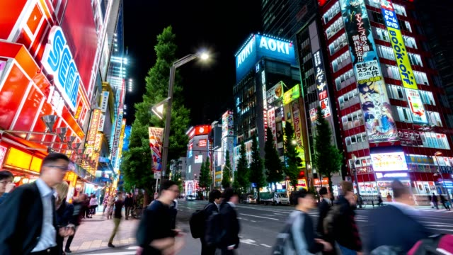 4k time-lapse: traveler pedestrian crowded walking across the crosswalk at akihabara district area, tokyo, japan. tilt up shot - akihabara station stock videos and b-roll footage