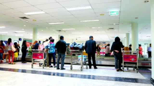 vidéos et rushes de hd time-lapse: les voyageurs de rejoindre leurs bagages de l'aéroport de la ceinture - voyage d'affaires