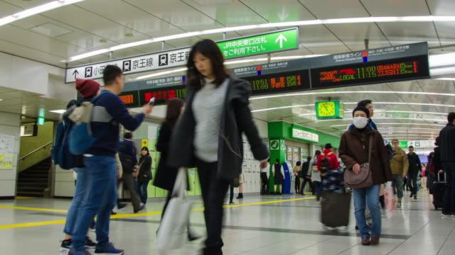 vídeos y material grabado en eventos de stock de 4 k time-lapse: viajero lleno de gente en la estación de shinjuku en tokio, japón. - señal de salida señal de dirección