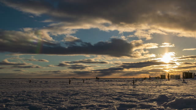 timelapse video of ice fishing in canada at sunset. - fishing stock videos & royalty-free footage