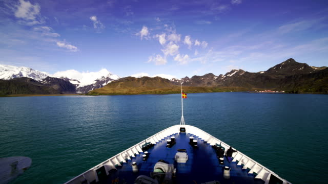 Time-lapse : View across bay to snow capped mountains with anchored boat in harbor