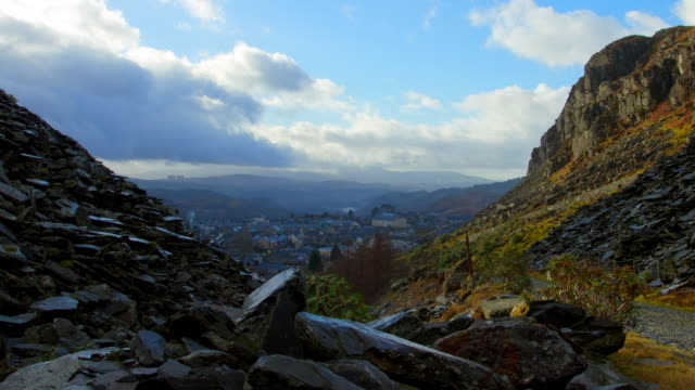 vídeos de stock e filmes b-roll de time-lapse view of blaenau in wales from the slate quarry. beautiful cloud movement and sunlight as camera pulls out . - país de gales