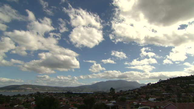 timelapse vision of hobart taken from howrah tasmania fluffy white clouds roll overhead throwing shadows onto the suburban houses below - cloud sky stock videos & royalty-free footage