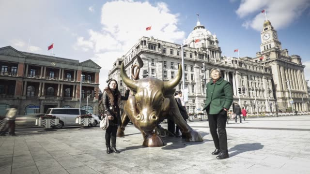 Timelapse visitors pose for photographers at a bronze statue of a Bull located on the Bund in Shanghai China on Tuesday Jan 31 2017